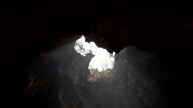 sunbeams shining in dark cave - кейвинг стоковые видео и кадры b-roll