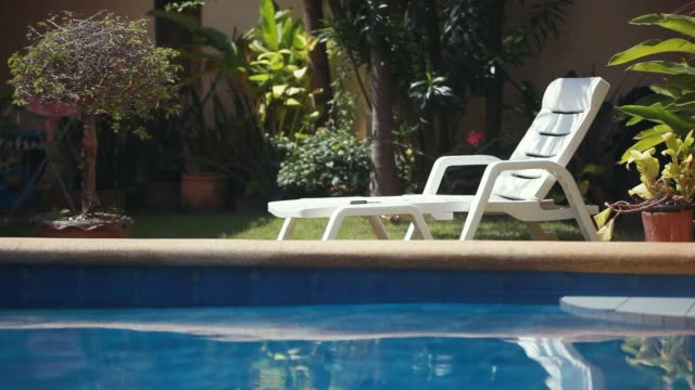 Sunbed lounger near the swimming pool. Tropical paradise. 1920x1080 Sunbed lounger near the swimming pool, Tropical paradise. lounge chair stock videos & royalty-free footage