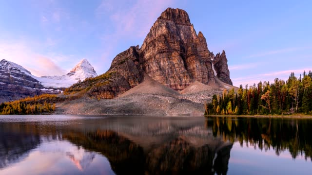 Sunburst lake and mount Assiniboine reflections in autumn forest on provincial park