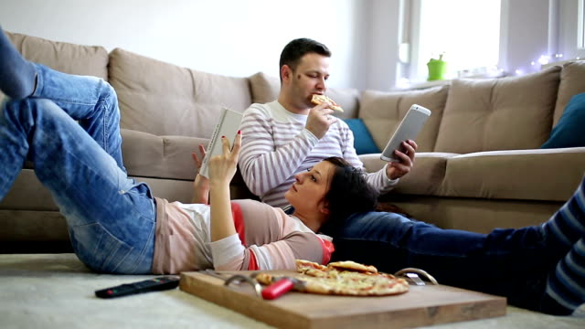 Sunday afternoon at home Young couple sitting on floor in living room, eating pizza, reading, surfing the net snack stock videos & royalty-free footage