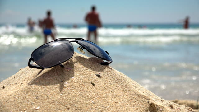 Sunglasses lying on tropical sand beach. party. Beautiful sea view wallpaper, background video