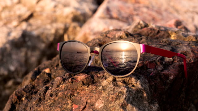 sunglasses which reflect a passing ship on sunset background video