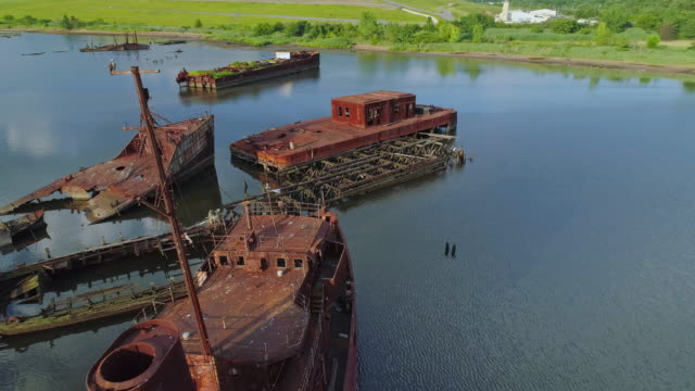 Sunk abandoned ships and shipwrecks on the Boat Graveyard in Arthur Kill tidal strait at the shore of Staten Island, New York City, USA. Aerial low-altitude video made by the drone, with the forward camera motion.