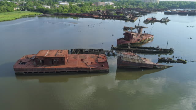Sunk abandoned ships and shipwrecks on the Boat Graveyard in Arthur Kill tidal strait at the shore of Staten Island, New York City, USA. Aerial low-altitude video made by the drone, with the panoramic camera motion.