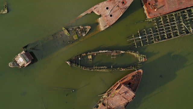 sunk rusty abandoned ships on the boat graveyard in staten island, new york city, usa. looking down, directly above aerial video made by the drone, with the spinning camera motion. - кораблекрушение стоковые видео и кадры b-roll