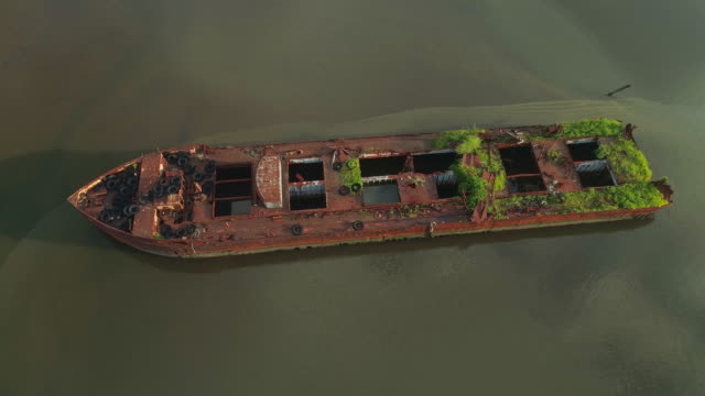 Sunk rusty abandoned ships on the Boat Graveyard in Staten Island, New York City, USA. Looking down, directly above aerial video made by the drone, with the spinning camera motion.