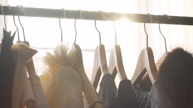 vídeos de stock, filmes e b-roll de luz solar entre cabides para roupas. estúdio de design solar - fashion