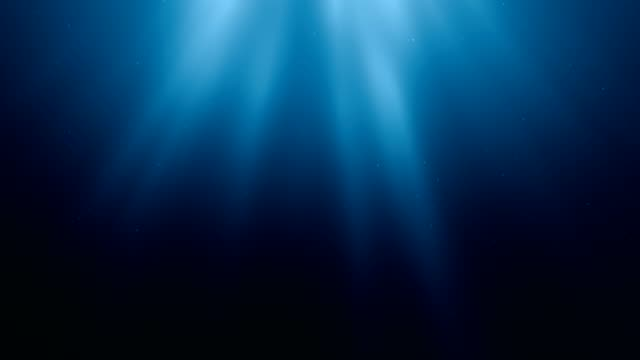 Sunlight rays shining through ocean surface. View from underwater. 3D rendered seamless loop animation.