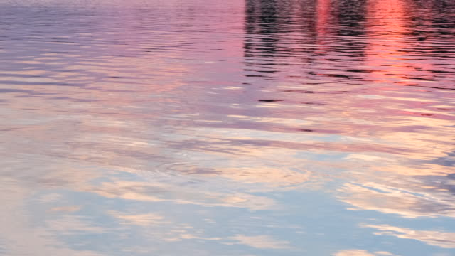 sunlight reflect on water surface.  amazing sunset over tropical beach. sparkling sunlight over the calm water. blurred reflected in sea sun ray. beautiful evening nature sea background - спокойная вода стоковые видео и кадры b-roll