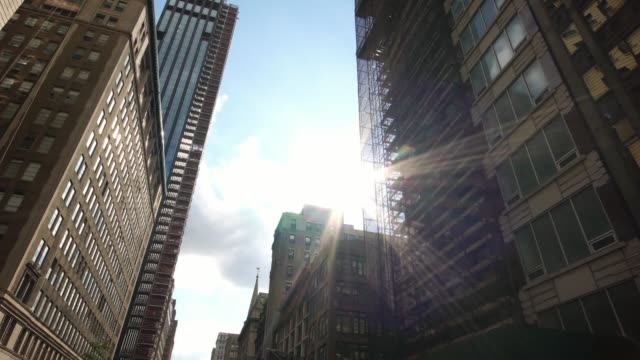 Sunlight reflecting in skyscrapers in NYC New York City Manhattan street dolly shot NYC New York City street, low angle pov glide moving shot low angle view stock videos & royalty-free footage