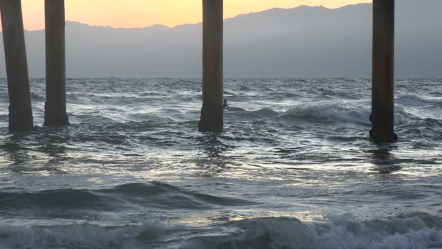 Sunlight reflecting on the waves under a pier Sunlight reflecting on the waves under a pier with the Santa Monica Mountains in the background, 4k b roll stock videos & royalty-free footage