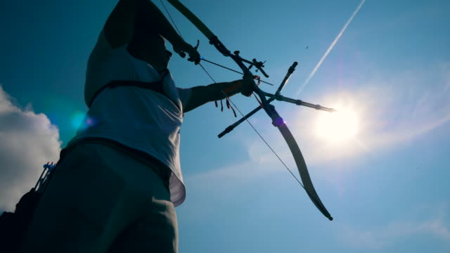 Sunlit sky and an archer in the process of aiming