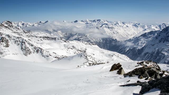 stockvideo's en b-roll-footage met zonnige dag boven wolken in winter besneeuwde alpen bergen. tijd lapse dolly schot over rotsen en snow drift - sneeuwkap
