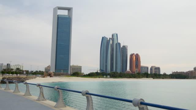 sunny day abu dhabi famous etihad towers sidewalk beach panorama 4k united arab emirates - uae national day стоковые видео и кадры b-roll