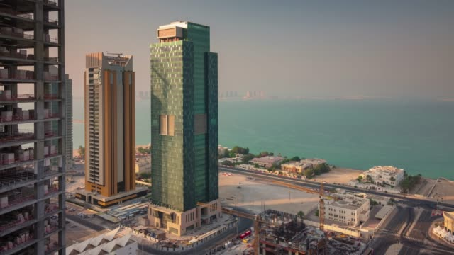 vidéos et rushes de panorama de la journée ensoleillée doha ville construction baie du centre sur le toit 4 temps k caduc qatar - doha