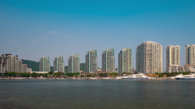 sunny day sanya city apartment complex riverside panorama 4k timelapse hainan island china