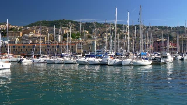 vídeos de stock, filmes e b-roll de opinião ensolarada do dia do porto genoa (genova), italy. baía de genoa, porto, iate no cais. uhd, 4k - marina