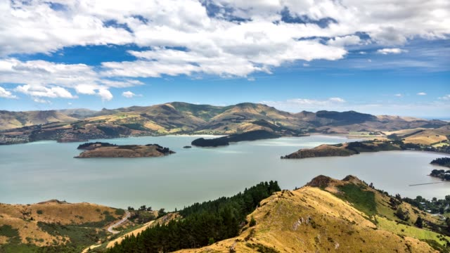 sunny landscape with clouds over sea bay and mountains in new zealand nature time lapse - christchurch nuova zelanda video stock e b–roll
