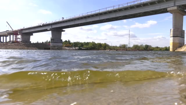 Sunny summer landscape with river, sandy beach and beautiful green trees on the river bank. Construction of a concrete bridge. Construction of an automobile bridge at a construction site.