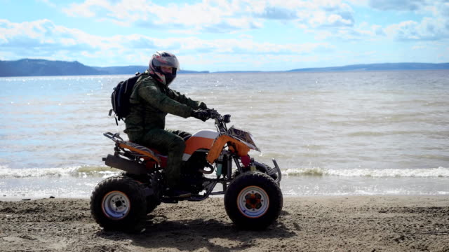Sunny weather. River bank. The man in a special uniform and crash helmet rides on the river bank the ATV video