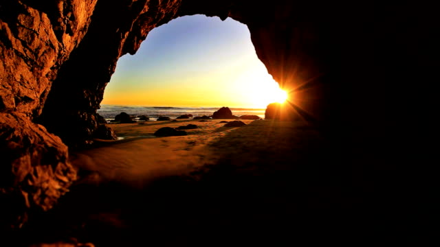 Sunrays in Beach Cave The sun begins to set as waves crash at the opening of a cave. cave stock videos & royalty-free footage