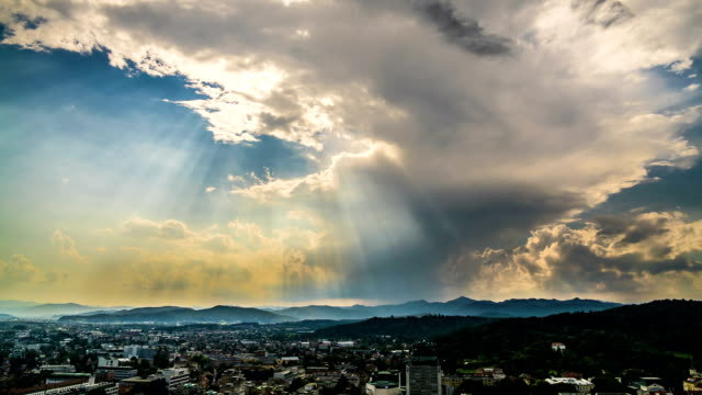 Sunrays penetrating clouds in heavenly sky above mountain resort city, timelapse video