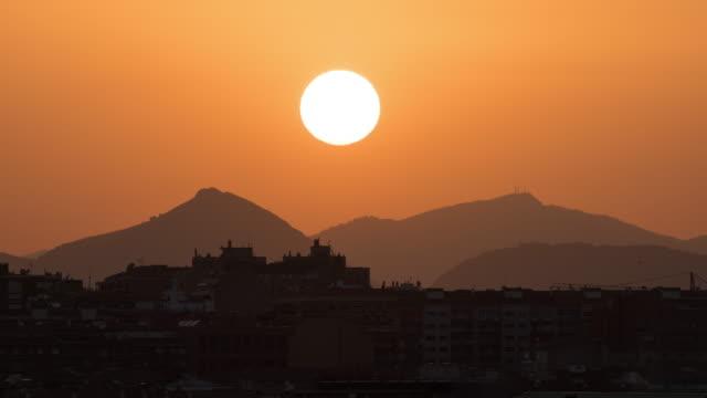 vidéos et rushes de lever et coucher du soleil au-dessus des montagnes et de la silhouette de bâtiments de ville - canicule