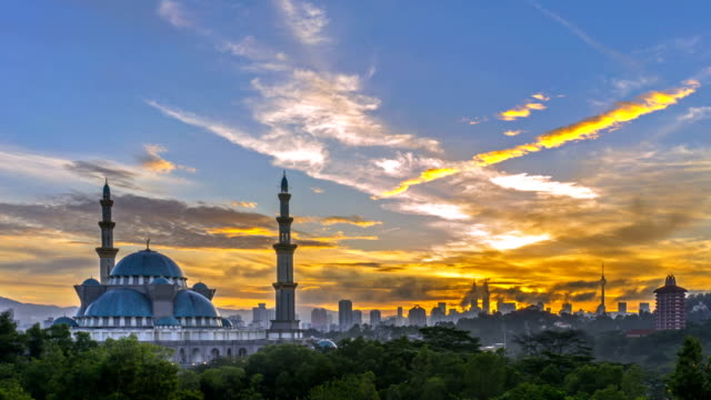 sunrise at federal mosque, kuala lumpur with silhouette kuala lumpur city skyline. - eid mubarak stock videos and b-roll footage
