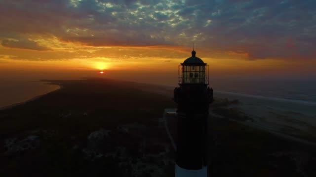 sonnenaufgang am leuchtturm von einer drohne - leuchtturm stock-videos und b-roll-filmmaterial