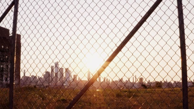 Sunrise at New York City with Manhattan skyline 4k Morning at NYC behind wire fence poverty stock videos & royalty-free footage