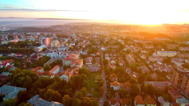 vídeos de stock, filmes e b-roll de nascer do sol backflight - sol nascente horizonte drone cidade