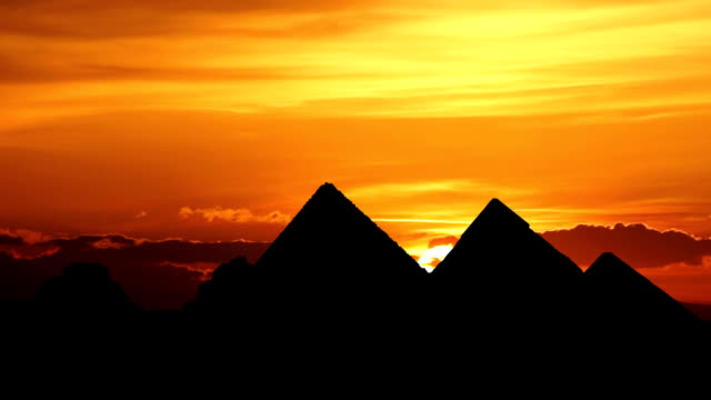 sunrise behind great pyramids in giza valley, cairo, egypt - 埃及 個影片檔及 b 捲影像