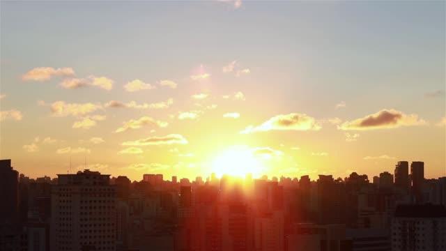 sunrise between buildings. - são paulo video stock e b–roll