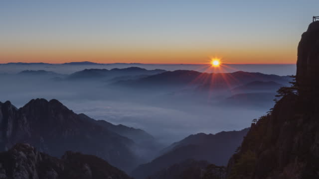 sunrise from bright top peak of  huangshan mountain - time lapse - trees in mist stock videos & royalty-free footage