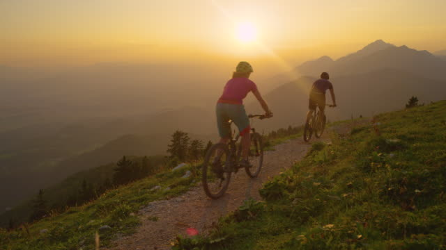 LENS FLARE: Sunrise illuminates valley as tourists go for a scenic bike ride. video