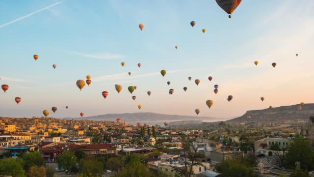 sonnenaufgang in kappadokien mit fliegendem ballon in kappadokien stadt skyline in goreme, türkei zeitraffer - zentralanatolien stock-videos und b-roll-filmmaterial