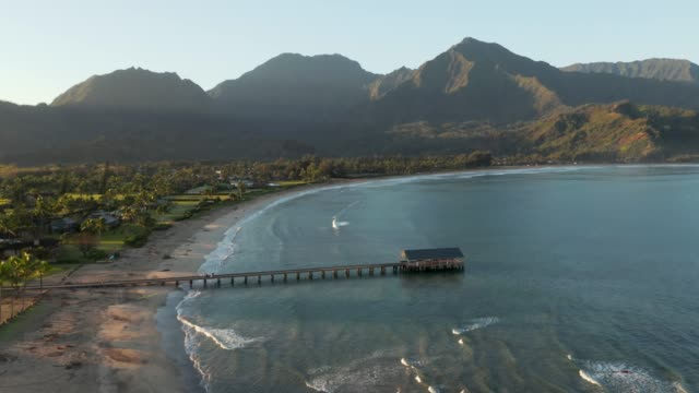 Sunrise lights the mountains as drone slowly descends towards the ocean surface while facing the on Hanalei bay on Hawaiian island of Kauai - video