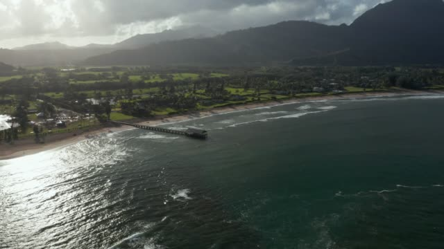 Sunrise lights the mountains as drone slowly zooms and moves towards the pier on Hanalei bay on Hawaiian island of Kauai - video