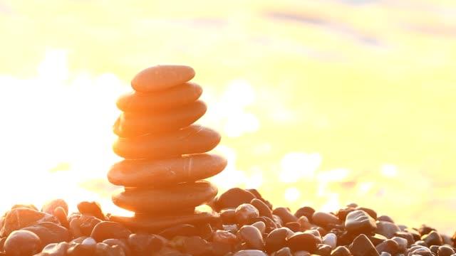 Sunrise on the sea and the pebble pyramid