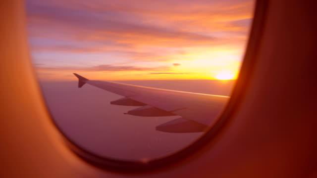 비행기 창에서 일출 또는 일몰 보기 항공기 날개 - 배경 초점 스톡 비디오 및 b-롤 화면