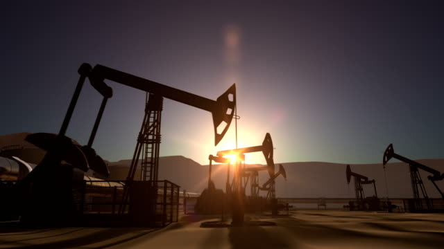 Sunrise over oil field with pumpjacks and pipeline Sunrise over oil field with oil pump jacks and oil pipeline oil and gas stock videos & royalty-free footage