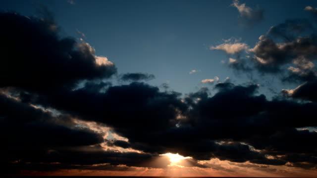 Sunrise over sea, dramatic clouds, time lapse video