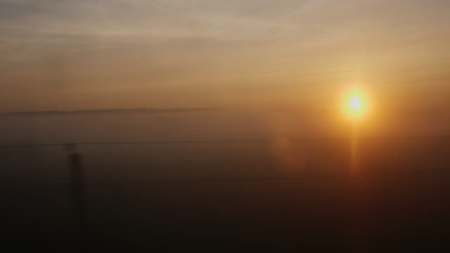 Sunrise over the countryside. View from the window of a moving train