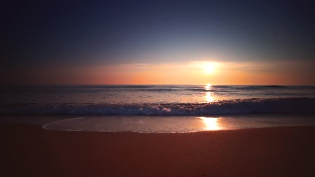Sunrise over the sea and beach. Waves washing the sand
