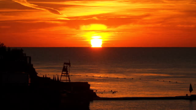 Sunrise over the sea. The coastline is visible Sunrise over the sea. The coastline is visible human back stock videos & royalty-free footage