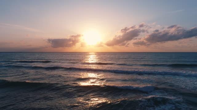 Sunrise over tropical exotic island beach and Caribbean sea. Ocean waves wash the sand