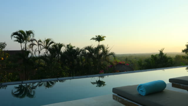 Sunrise panning of luxurious villa property with infinity swimming pool