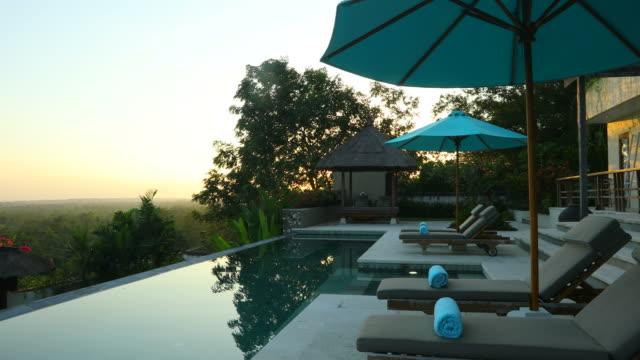 日の出は、スイミング プール付けの豪華なヴィラのパン - 別荘点の映像素材/bロール