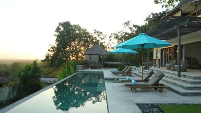 sunrise panning of luxurious villa property with swimming pool - вилла стоковые видео и кадры b-roll