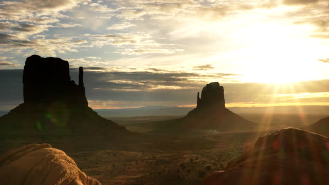 sunrise shot of the mittens with lens flare at monument valley